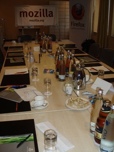 Konferenztisch mit Getränken und dem großen Mozilla-Banner im Hintergrund