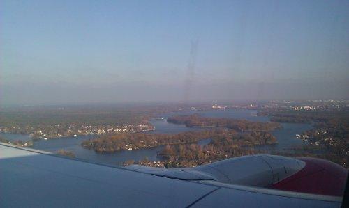Blick aus dem Flugzeug mit Blick auf einen Flügel und die Wälder vor Berlin